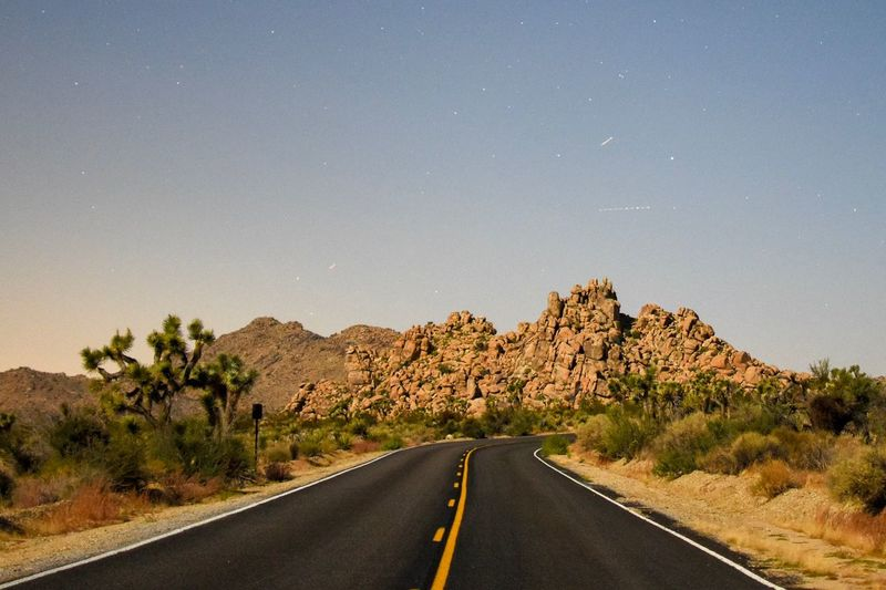 Empty road leading towards rock formations against clear sky