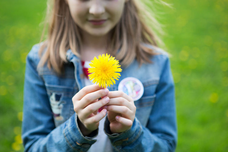 Midsection of girl holding yellow flower at park