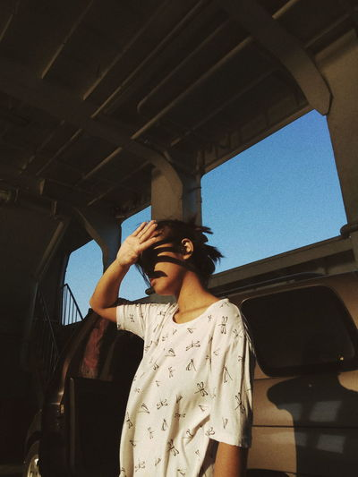 Young Woman Shielding Face While Standing In Motor Home