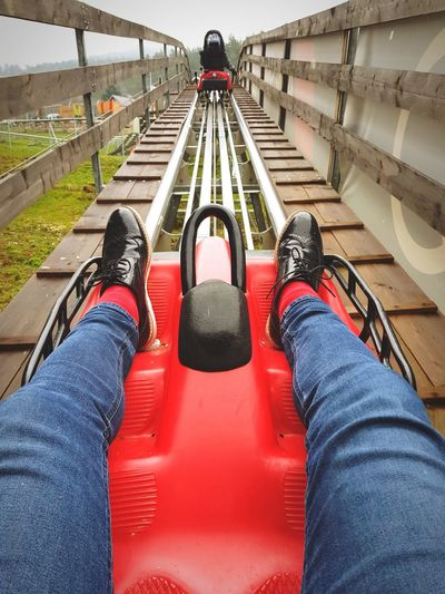 Low Section Of Person Sitting In Amusement Park Ride