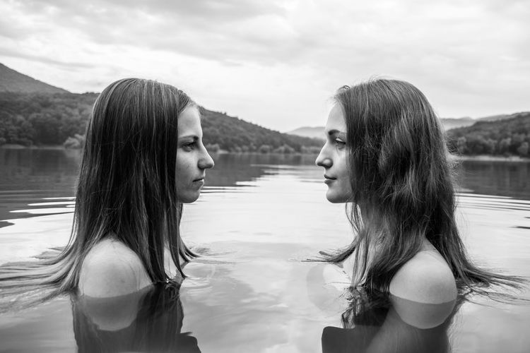 Profile view of shirtless female friends face to face in lake