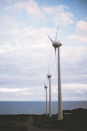Wind turbines on sea shore against sky