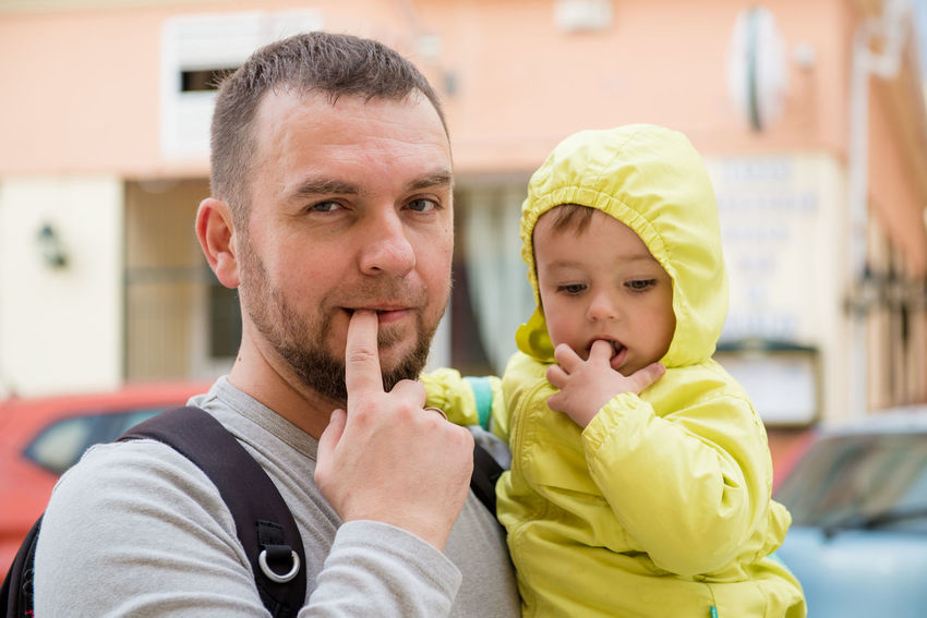 Father and little daughter outdoors 2 Years Old Family Funny Bearded Childhood Cute Daughter Family With One Child Father Finger In Mouth Fingers Generation Handsome Headshot Holding Little Girl Looking At Camera Love Mid Adult Men Outdoors Portrait Pose Real People Street Togetherness