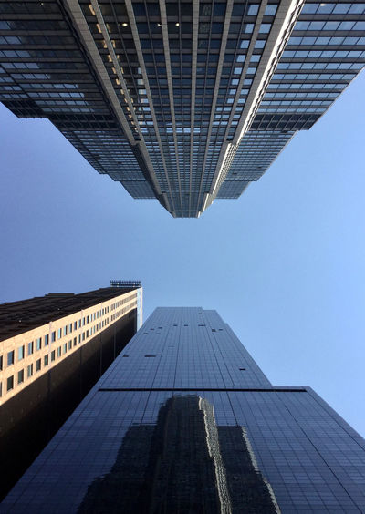 Low angle view of modern buildings against blue sky in new-york, manhattan