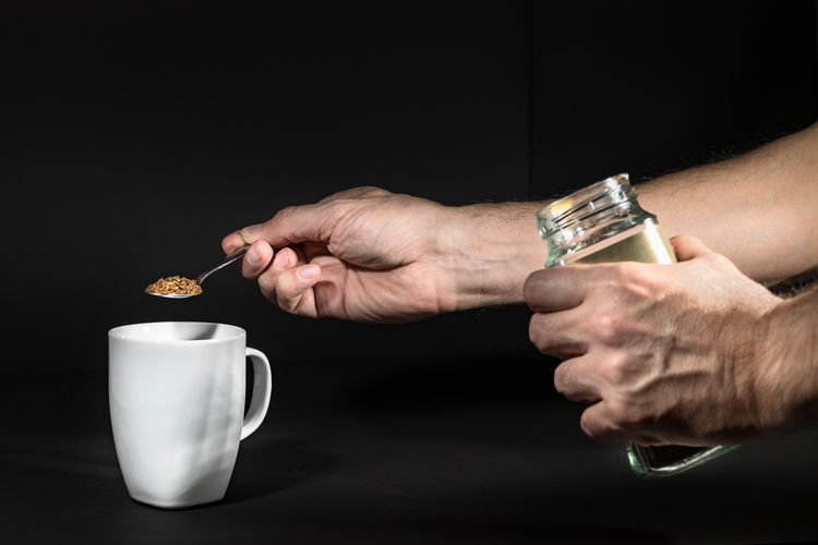 Human Hand Hand Human Body Part Drink Black Background Holding Studio Shot Food And Drink Adult Cup Indoors  One Person Mug Men Refreshment Close-up Wristwatch Human Limb Finger Drinking
