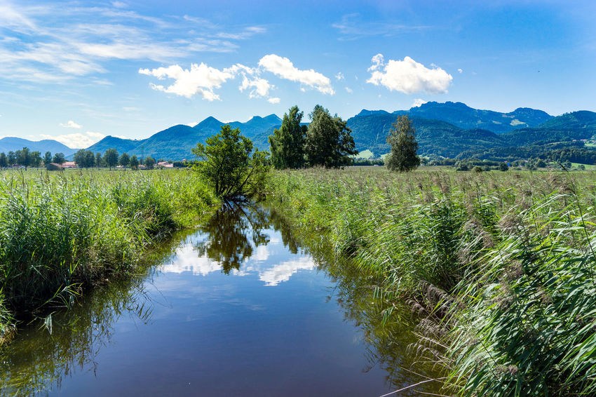 Small River Beauty In Nature Blue Cloud - Sky Day Grass Green Color Growth Landscape Mountain Mountain Range Nature No People Outdoors Plant Reflection Scenics Sky Tranquil Scene Tranquility Tree Water