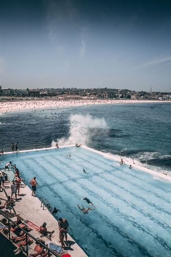 High Angle View Of People In Swimming Pool By Sea Against Sky During Sunny Day