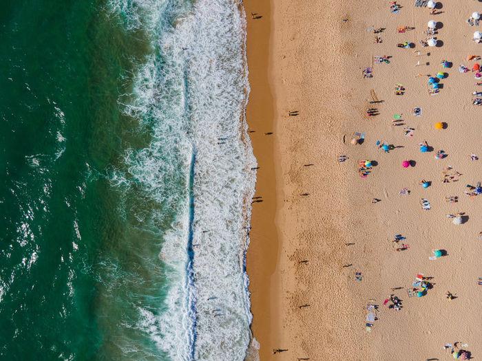 Vacationers fill praia princesa in lisbon