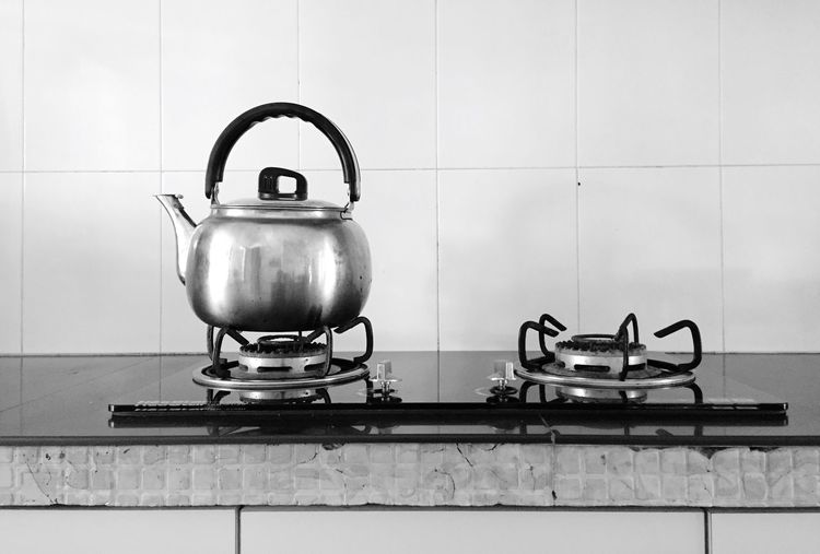 Kettle And Stove Against Wall On Counter In Kitchen