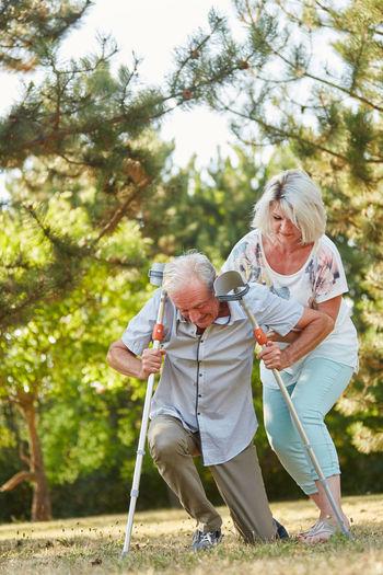 Woman Helping Senior Man At Park