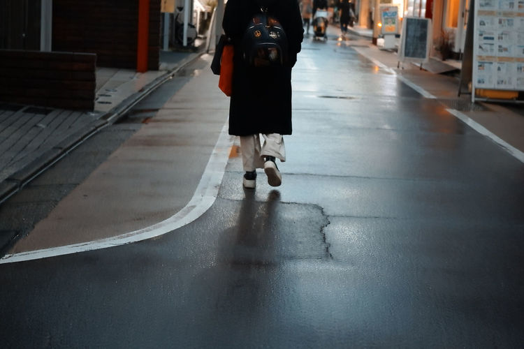 Low section of woman walking on road in city