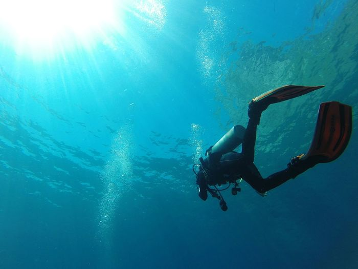 Low Angle View Of Woman Scuba Diving In Sea