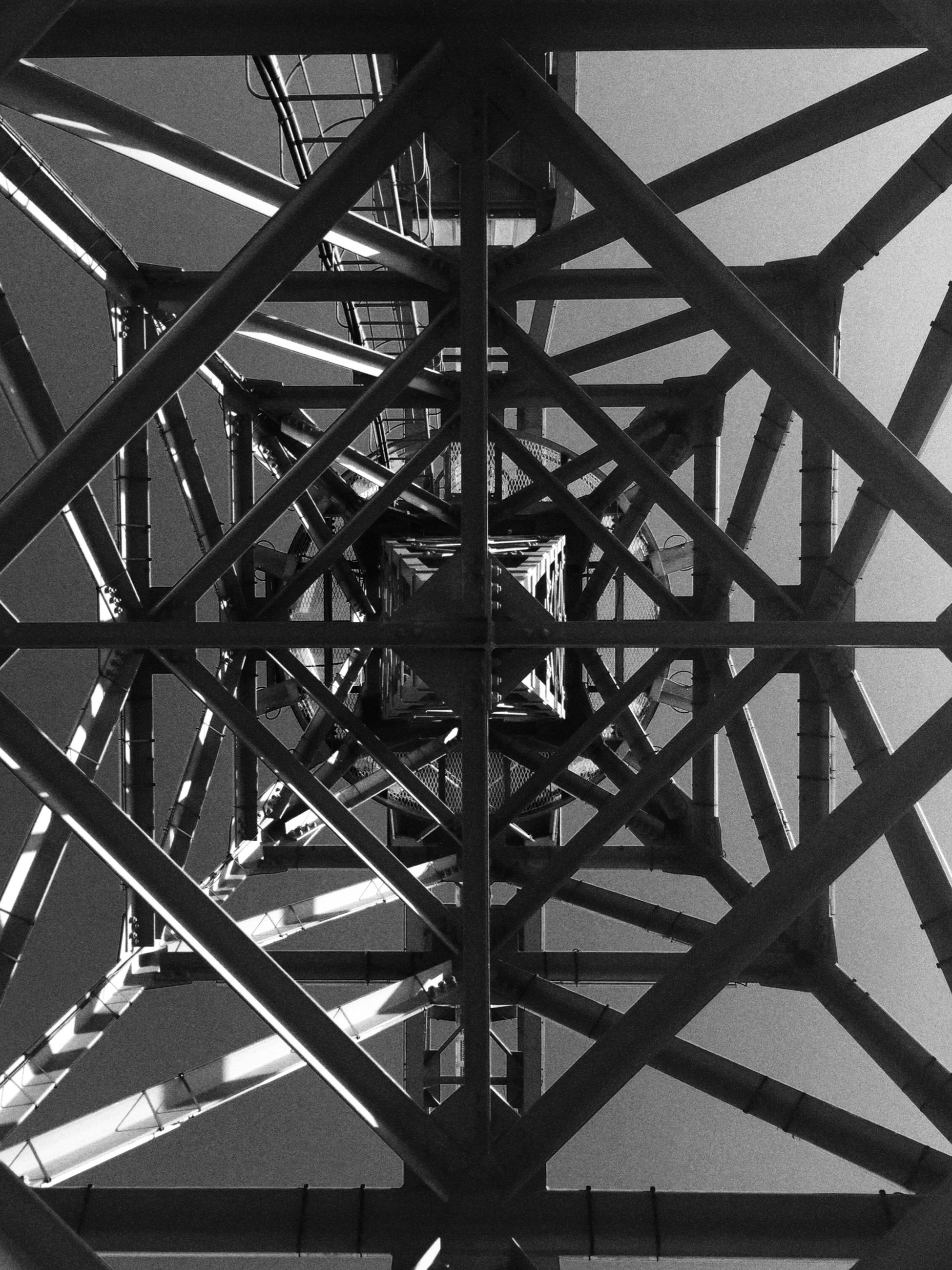low angle view, built structure, metal, architecture, metallic, connection, engineering, grid, bridge - man made structure, sky, no people, day, clear sky, pattern, outdoors, structure, transportation, diminishing perspective, directly below, sunlight