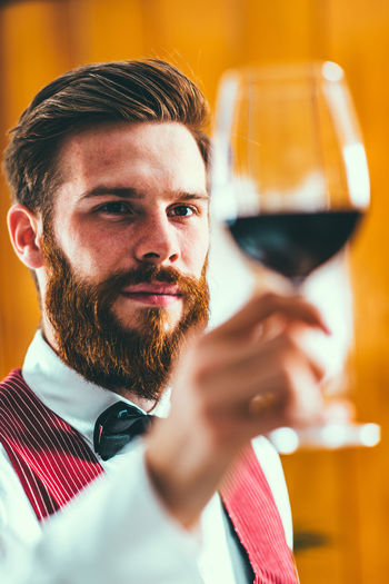 Close-up sommelier holding wine in glass