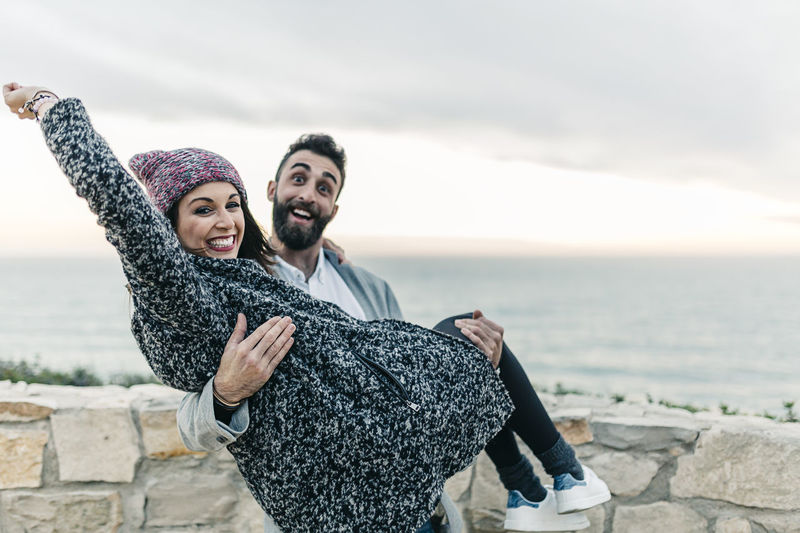 Portrait of smiling man carrying woman against sea