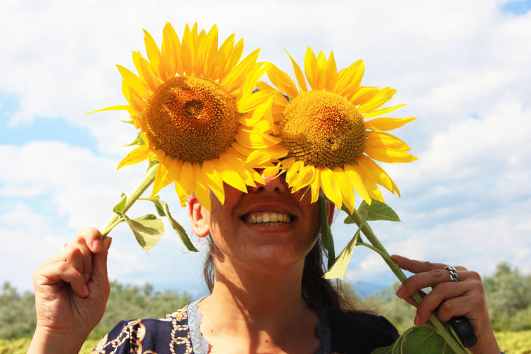 Close-up portrait of smiling woman holding sunflower against sky