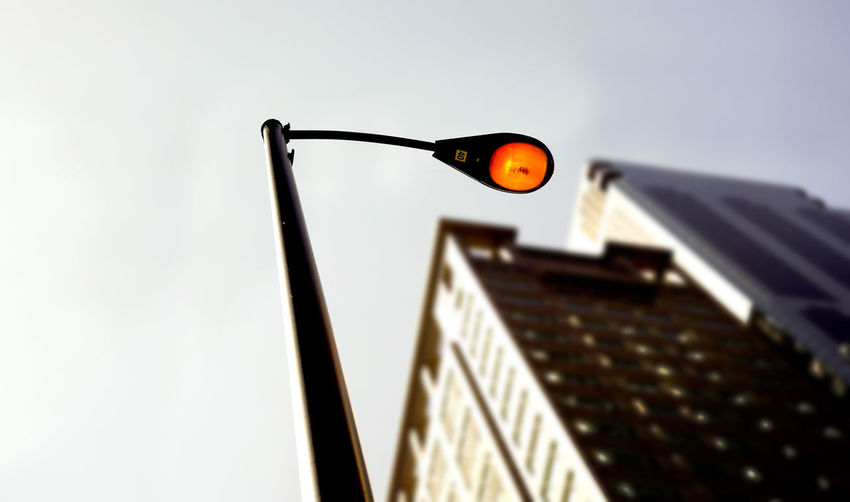 Low angle view of illuminated street light against sky in city during sunset