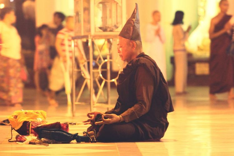 Side view of monk meditating while sitting on floor
