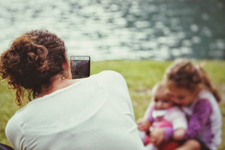 Rear view of woman taking picture of siblings
