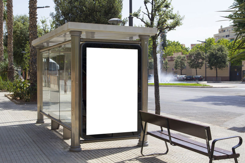 Blank billboard in the street Advertising Bench Branding Advertisement Architecture Billboard Blank Built Structure Bus Stop City Communication Day Empty Footpath Mock Up No People Outdoors Street Sunlight Tree White Color