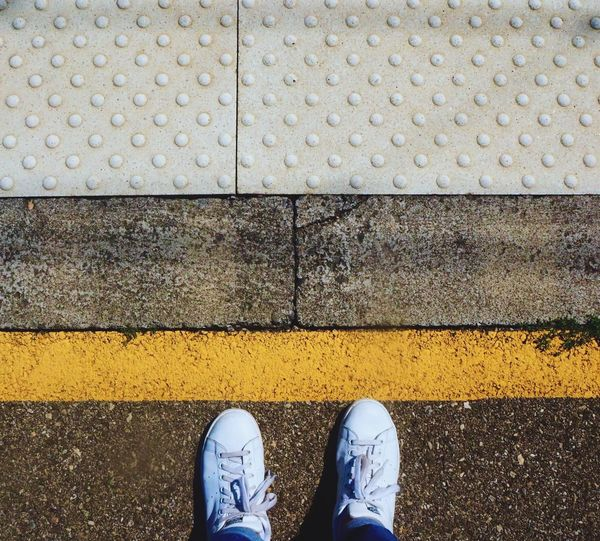 Low Section Of Person Wearing Sneakers Standing At Railroad Station