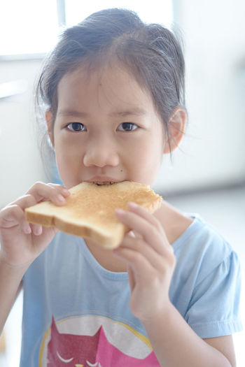 Portrait of girl eating bread at home