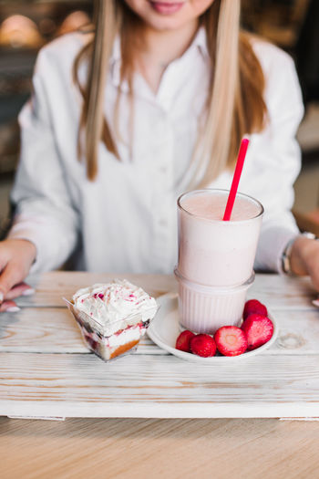 Midsection of woman holding ice cream on table