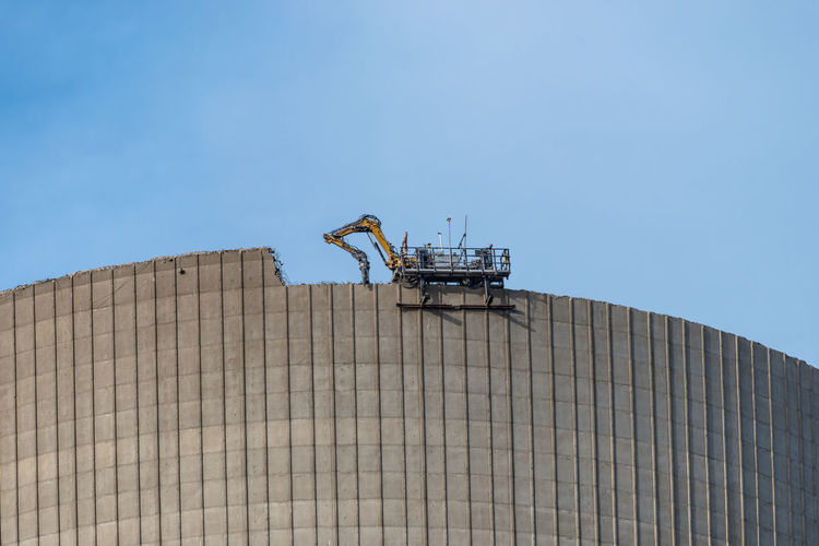 Demolition of the atomic chimney. remote controlled excavator with shears works from above.