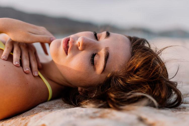 Carefree young woman in yellow bikini lying on rock at beach