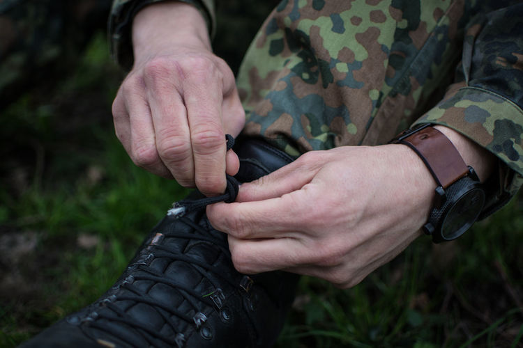 Low Section Of Army Soldier Tying Shoe On Grassy Field