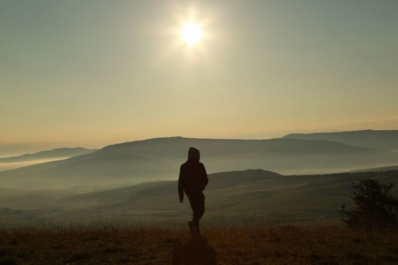 Silhouette person walking on mountain against sky during sunrise