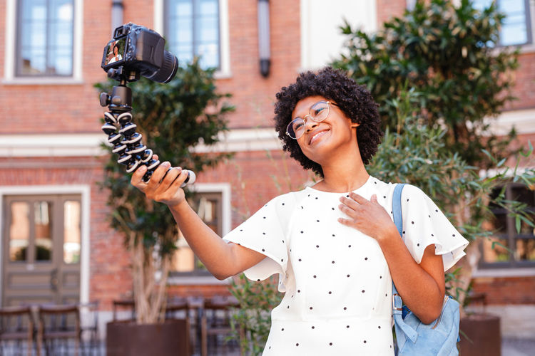 Smiling teenage girl taking selfie with camera while standing against building