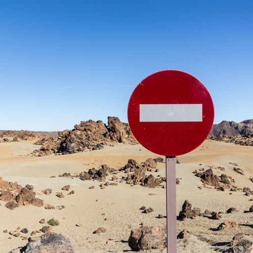 no trespassing sign in desert landscape Blue Blue Sky Clear Sky Close-up Day Desert Guidance Information Information Sign Landscape Nature No People No Trespassing No Trespassing Sign Outdoors Pole Red Road Sign Sign Sky Tranquil Scene Tranquility Warning Sign