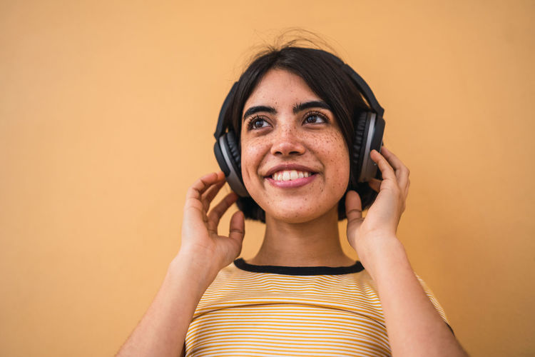 Close-up of smiling woman wearing headphones standing against beige background
