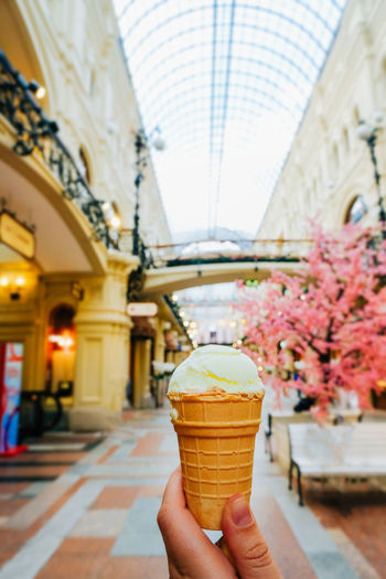Midsection of person holding ice cream against building