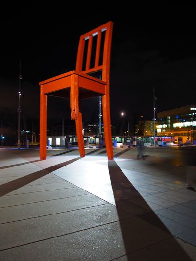 The Broken Chair sculpture stands outside the United Nations in Geneva, Switzerland and symbolises opposition to land mines and cluster bombs Architecture Building Exterior Business Finance And Industry Chair City Cityscape Culture Night No People Outdoors Sculpture United Nations Urban Skyline