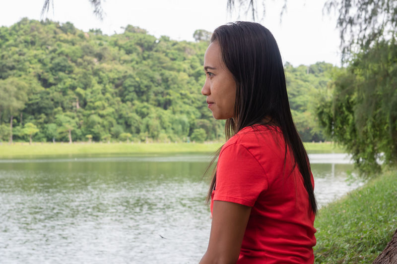 Side view of young woman standing by lake against trees