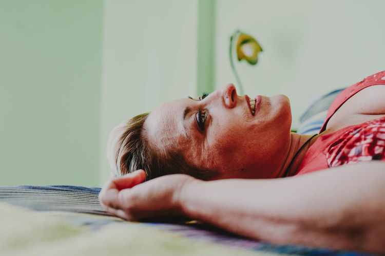 Close-up of young woman lying on bed at home