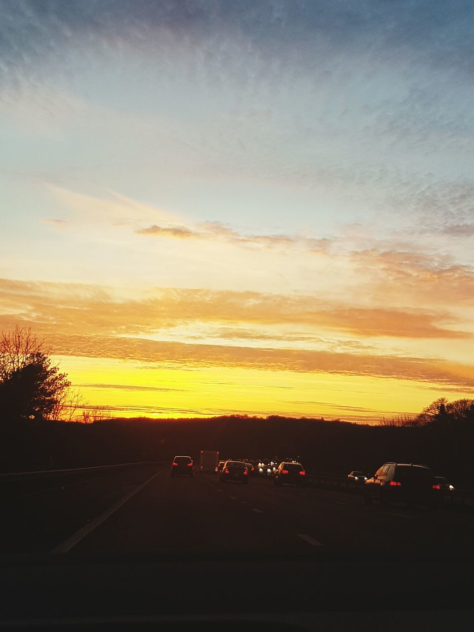 sunset, car, transportation, road, sky, land vehicle, silhouette, scenics, orange color, no people, the way forward, mode of transport, nature, beauty in nature, car point of view, cloud - sky, landscape, outdoors, day