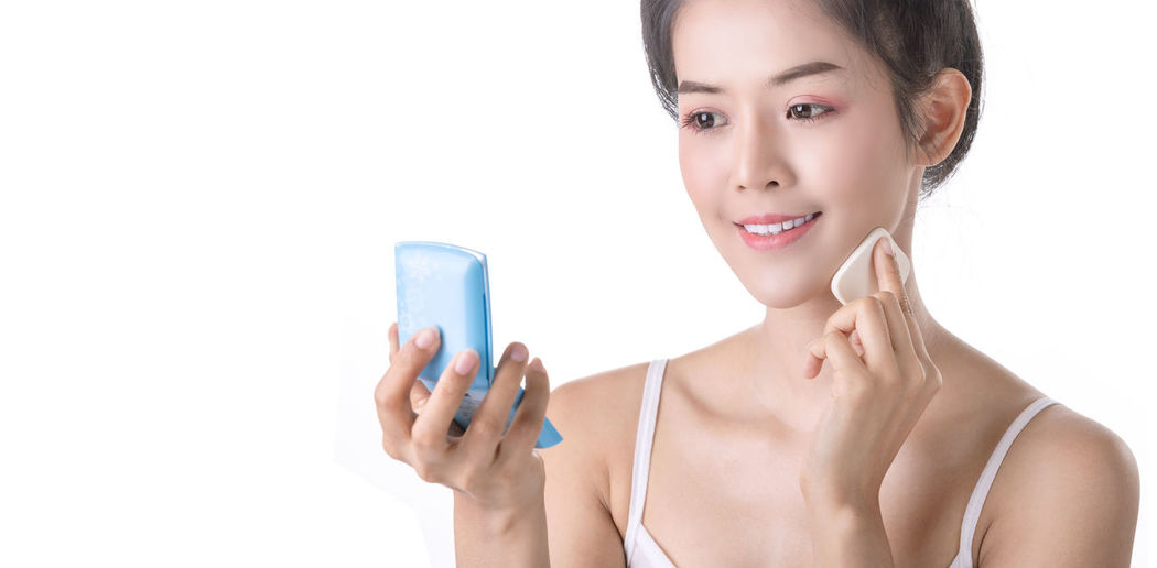 Portrait of woman holding mobile phone against white background