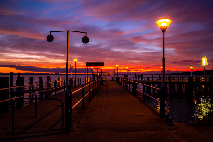 Street lights on pier by sea against sky during sunset