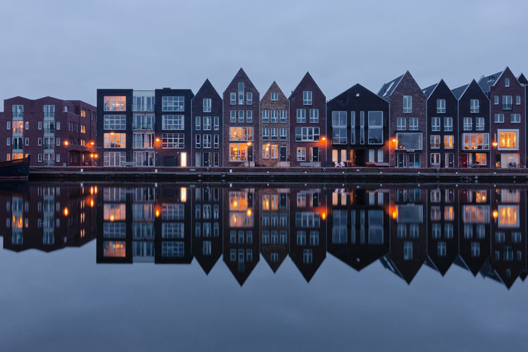 Residential houses along Kelderwindkade in Haarlem at the blue hour Haarlem Kelderwindkade Netherlands Architecture Building Building Exterior Built Structure Canal Dusk Illuminated Lake Nature Night No People Outdoors Reflection Residential District River Row House Side By Side Sky Standing Water Symmetry Water Waterfront