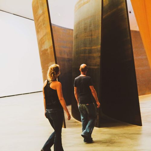 Rear view of man and woman walking on building