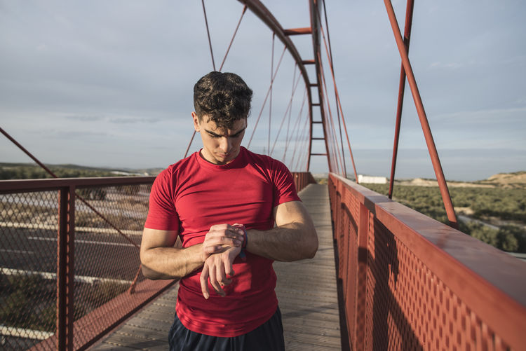Athlete checking the time while standing on footbridge against sky