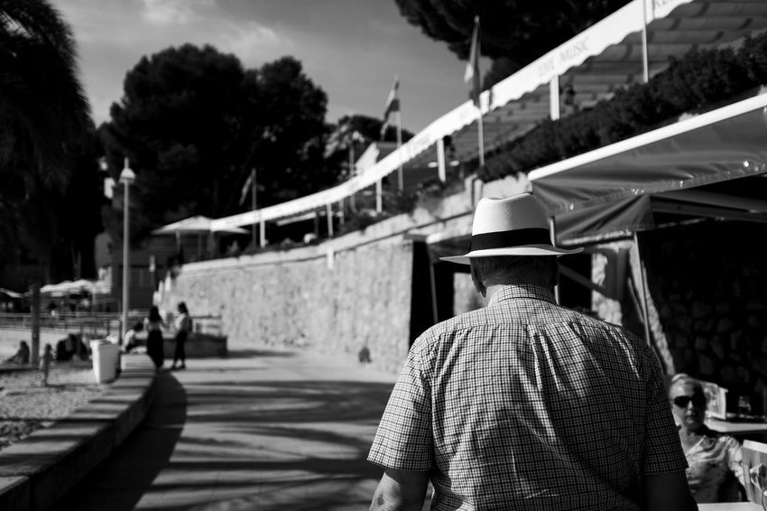 Fourdayspalma Monochrome Nature Outdoors Rear View Men Real People Incidental People Focus On Foreground People Hat Lifestyles Day Clothing Tree Leisure Activity Architecture Walking Transportation Sunlight Built Structure