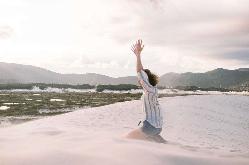 Side view of woman with arms raised kneeling on sand against cloudy sky