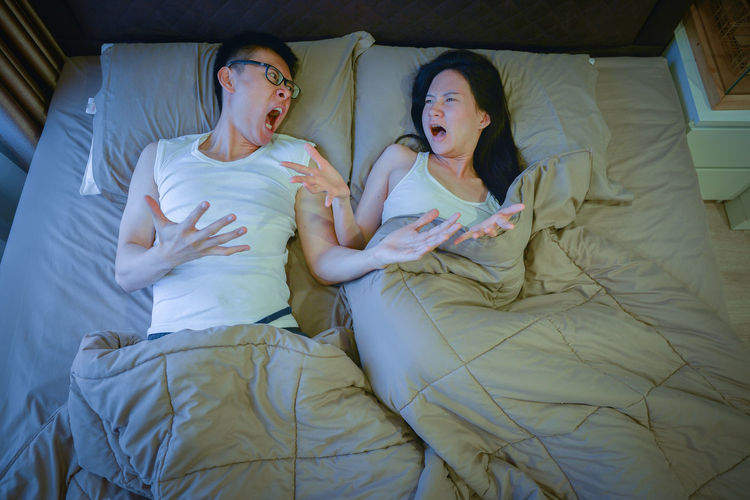 High Angle View Of Couple Screaming While Lying On Bed At Home