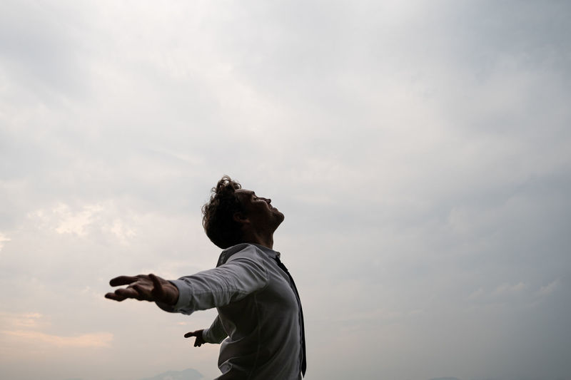 Side view of man with arms outstretched standing against sky