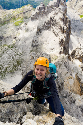 High angle portrait of smiling woman climbing mountain