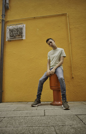 Full length of young man leaning against wall
